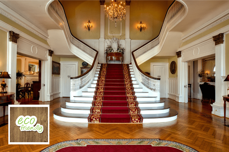 Beautiful entryway of mansion with carpeted steps and pristine wood floors